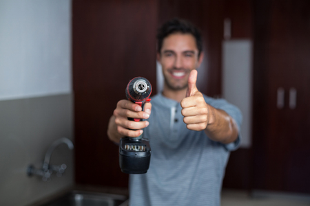 hand drill: Portrait of smiling man showing thumbs up while holding cordless hand drill at home Stock Photo
