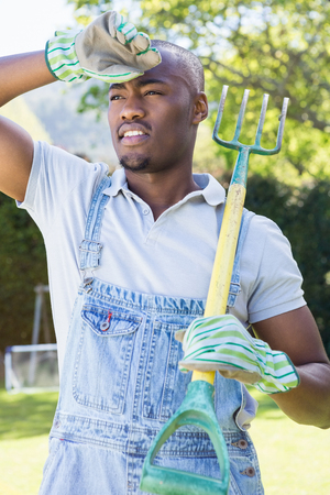weekend activity: Young man posing with rake in the garden