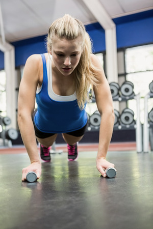 push ups: Determined woman doing push ups at gym Stock Photo
