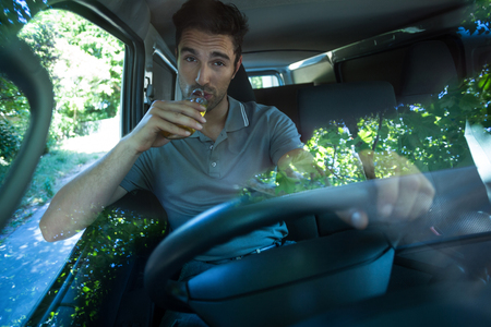 drinking driving: Portrait of slumped man drinking alcohol while driving car