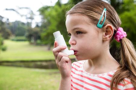 asma: Chica usando un inhalador de asma en el parque