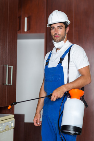 sprayer: Portrait of confident pest worker holding sprayer in kitchen