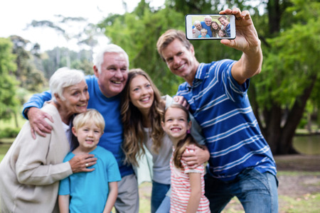 multigeneration: Multi-generation family taking a selfie in the park on a sunny day Stock Photo