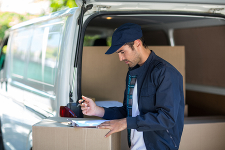 person writing: Side view of delivery person writing in clipboard while standing by van Stock Photo