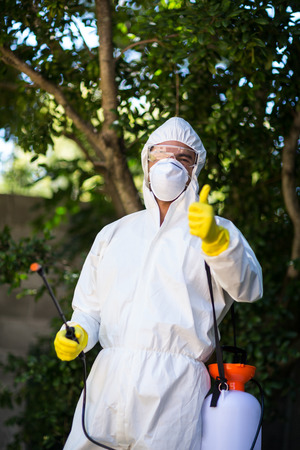 Portrait of man showing thumbs up while holding pesticide sprayer in lawn