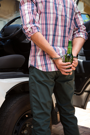 Man handcuffed behind his back for drinking and driving Stock Photo