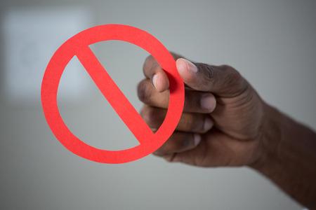 interdiction: Une main tenant un signe d'interdiction � la maison