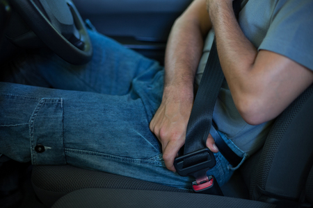 fastening: Midsection of driver fastening car seat belt