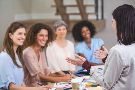 middleaged: Woman giving presentation to her colleagues in office