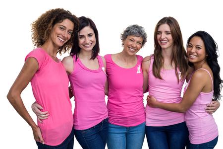 Mujeres sonrientes en trajes de color rosa posando para la conciencia del cáncer de mama en el fondo blanco Foto de archivo - 54924152