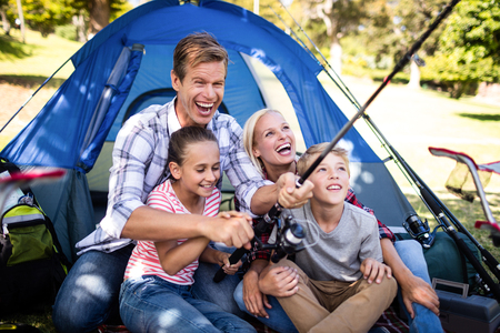 family bonding: Family on a camping trip fishing outside their tent
