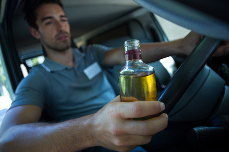 slumped: Slumped man holding alcohol bottle while driving car