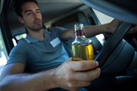 slumped: Slumped man holding alcohol bottle while driving car