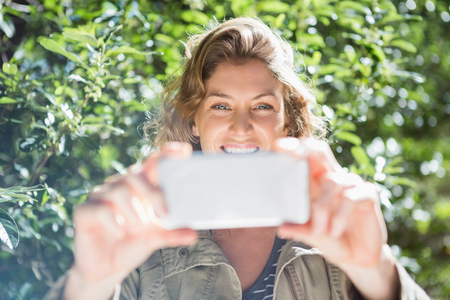 adventuring: Smiling woman taking selfies in the countryside