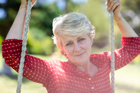 weekend activity: Close-up of a senior woman sitting on a swing in park