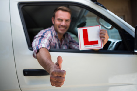 learner: Portrait of young man gesturing thumbs up holding a learner driver sign