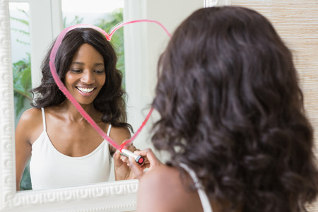 woman mirror: Beautiful young woman drawing big heart on mirror with lipstick Stock Photo