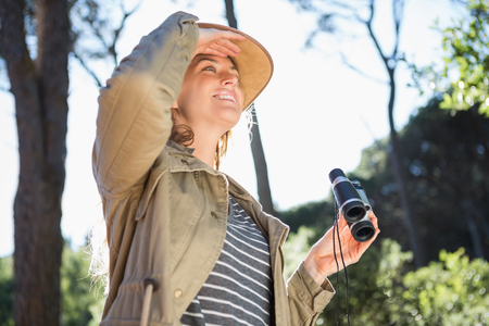using binoculars: Woman using binoculars in the countryside