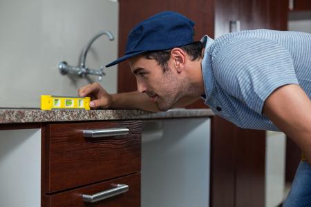 spirit level: Man using spirit level while bending in kitchen