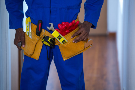 Mid section of handy man wearing tool belt at home Stock Photo
