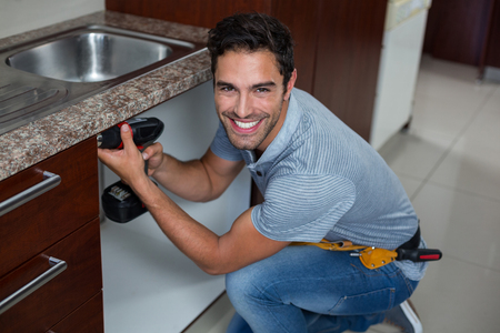 hand drill: Portrait of cheerful man using cordless hand drill at home