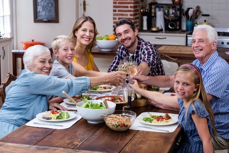 multigeneration: Multi-generation family toasting glass of wine while having meal Stock Photo