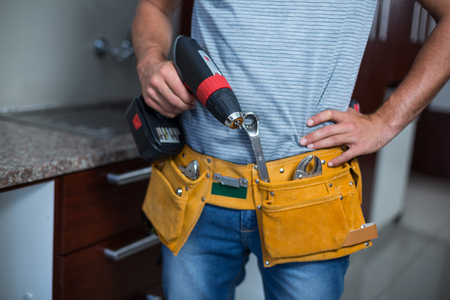 hand drill: Midsection of man holding cordless hand drill at home