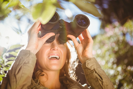 using binoculars: Woman using binoculars in the countryside