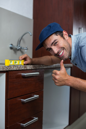 spirit level: Portrait of smiling man showing thumbs up while using spirit level in kitchen Stock Photo