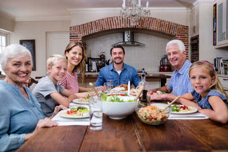 multigeneration: Multi-generation family having meal in kitchen at home Stock Photo
