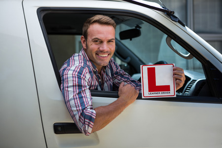 learner: Portrait of young man holding a learner driver sign
