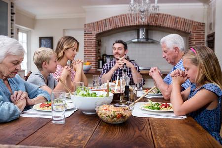 familia orando: familia multigeneracional que ruega antes de tener comida en su casa