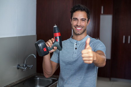 hand drill: Portrait of happy man showing thumbs up while holding cordless hand drill at home