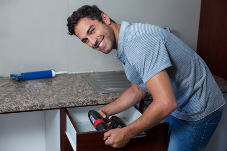 hand drill: Portrait of happy man using cordless hand drill at home