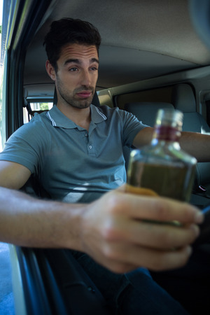 slumped: Slumped man with alcohol bottle while driving car
