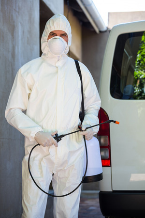 protective: Pest control man in protective workwear standing behind a van Stock Photo