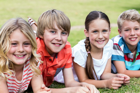 weekend activity: Portrait of happy children lying on grass in park Stock Photo