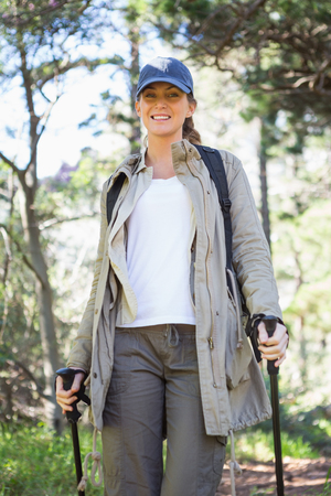 adventuring: Smiling woman nordic walking in the countryside