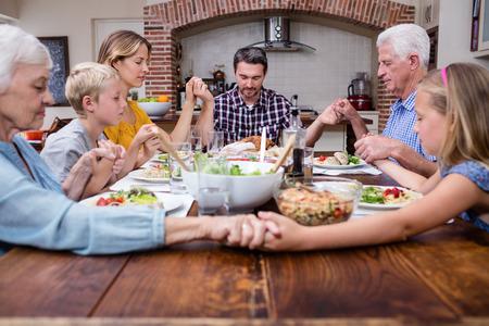 family praying: familia multigeneracional que ruega antes de tener comida en su casa