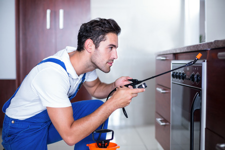 Man spraying insecticide on oven in kitchen