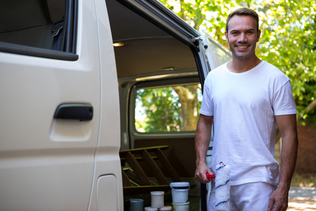 redecorating: Portrait of painter holding paint roller standing near his van