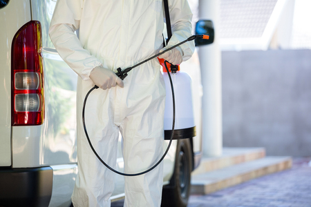 Mid section of pest control man standing next to a van on a street Stockfoto