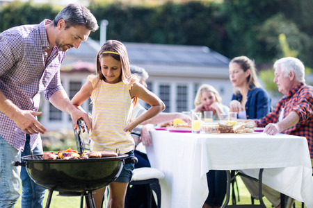 barbecue grill: Father and daughter at barbecue grill while family having lunch in the garden