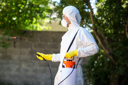 Side view of worker wearing protective suit using pesticide in back yard Stock Photo