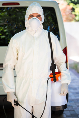 protective workwear: Pest control man in protective workwear standing behind a van Stock Photo