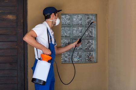 crop sprayer: Worker spraying chemical on window of house