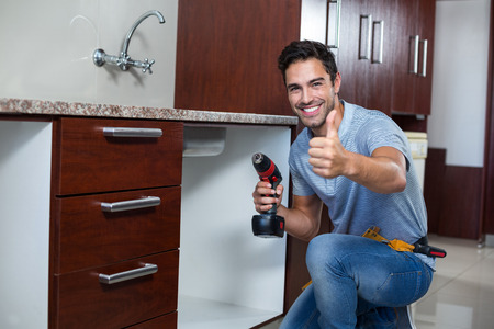 hand drill: Portrait of cheerful man showing thumbs up while using cordless hand drill at home