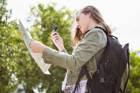 adventuring: Woman using map and compass in the countryside Stock Photo
