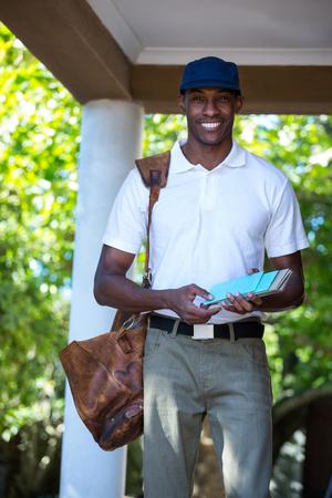 delivering: Portrait of happy postman delivering letter Stock Photo