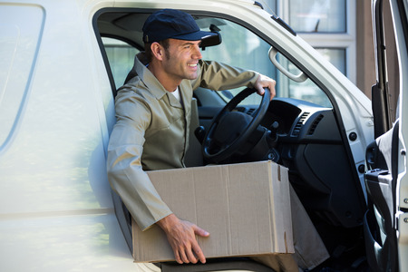 getting out: Delivery man with parcel getting out from van